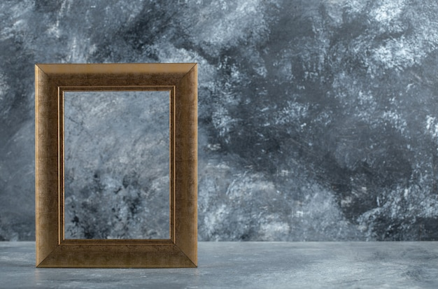 Empty golden picture frame on marble.
