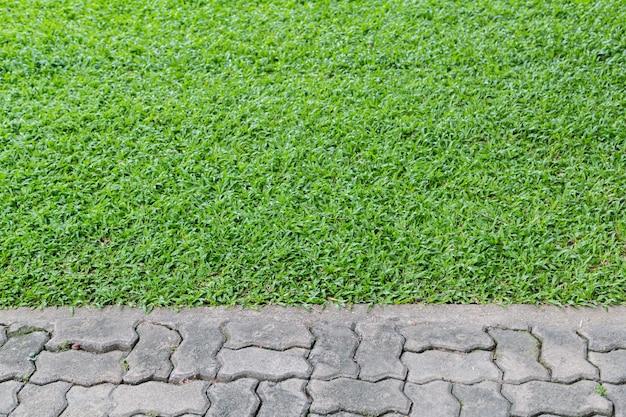 Пустой серый кирпич с зеленой травой для фона