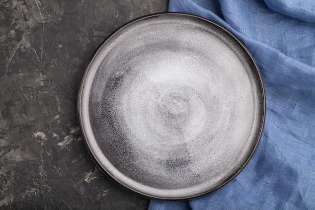 검은 콘크리트 배경과 파란색 리넨 섬유에 빈 회색 세라믹 접시. 평면도, 클로즈업, 평평하다.