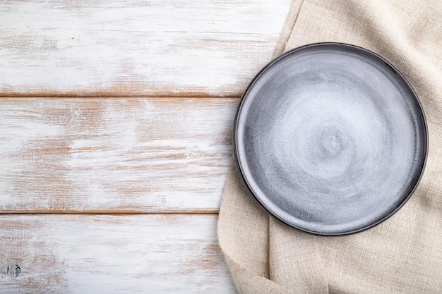 Пустая серая керамическая тарелка на белом деревянном фоне и льняной ткани