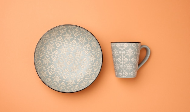 空の灰色のセラミックスーププレートとオレンジ色の背景、調理器具、上面図の空のカップ