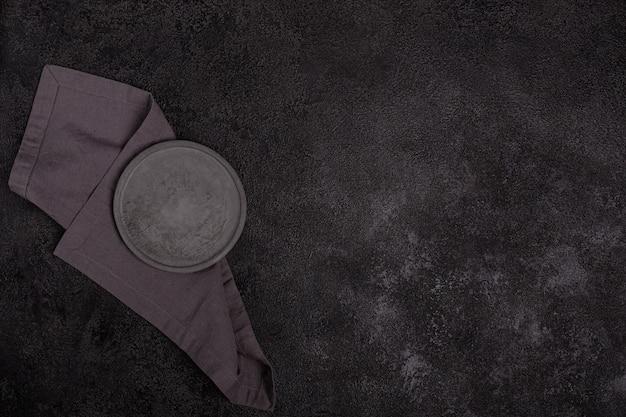 An empty gray concrete plate on a dark black background. a gray linen napkin.