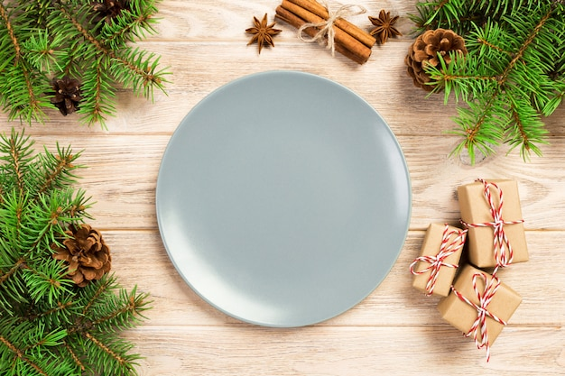 Empty gray matte plate on wooden  with christmas decoration, round dish, new year concept