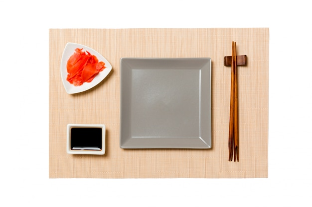 Empty gray square plate with chopsticks for sushi, ginger and soy sauce on brown sushi mat