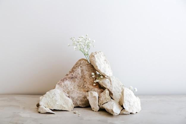빈 회색 돌 타워 연단입니다. 제품 프레젠테이션을 위해 돌 꽃 모형으로 만든 베이지색 콘크리트 배경에 돌 받침대가 표시됩니다.