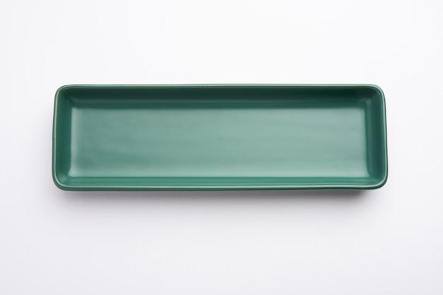 Пустая зеленая керамическая прямоугольная тарелка, изолированная на белой поверхности