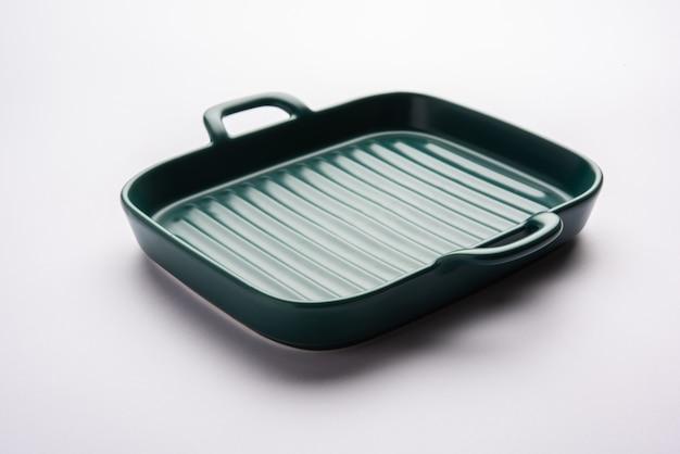 白または灰色の表面上に分離された空の緑色のセラミックサービングボウルまたは耐熱皿