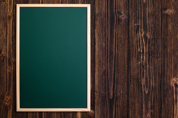 Empty green chalkboard with wooden frame on wood