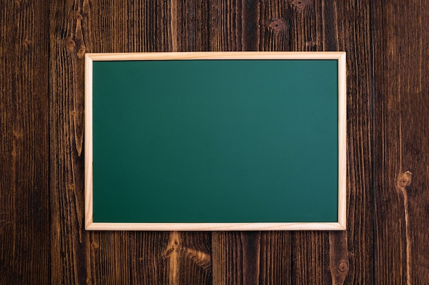 Empty green chalkboard with wooden frame on wooden desk