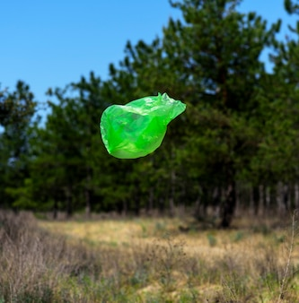 Empty green garbage bag flies against the background of green pines