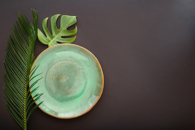 Empty green plate on black background. luxury dinner plate served with asian grunge style tropical palm leaves monstera plant. mock up ceramic plate. top view copy space. high quality stock photo