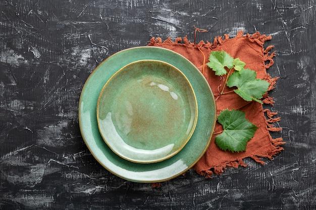 空の緑のプレートは、ブドウの葉の植物のテーブルナプキンを添えて。地中海料理のワインレストランでの豪華なディナーのためのモックアップテンプレートプレート。ダークブラックのコンクリートテーブルまたはチョークボード。