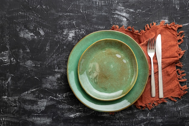 Empty green plate served with knife, fork and table napkin. mockup template plate for luxury dinner with copy space on dark black concrete table top view.