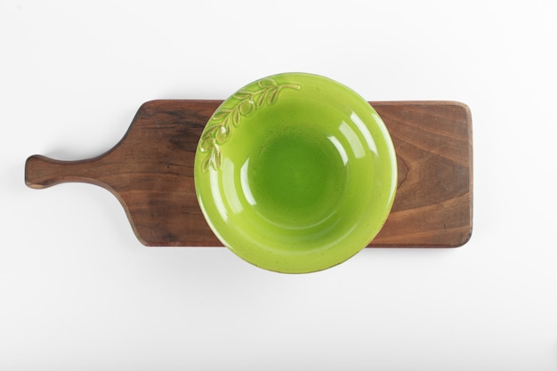 An empty green saucer on a white table on a wooden board