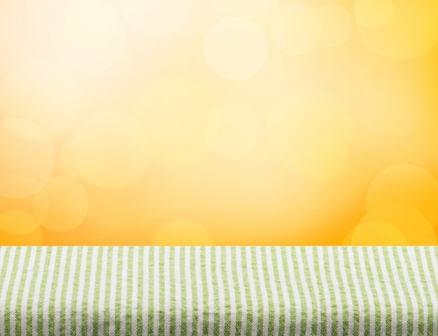 Empty green table cloth top at orange bokeh light background
