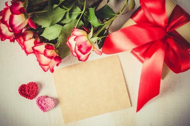 Пустая открытка, красные розы и подарочная коробка