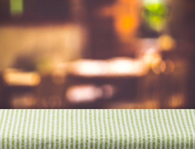 Empty grenn tablecloth on table and blurred restaurant bokeh light background