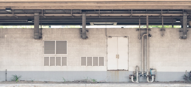 Empty grey industrial concrete wall with metal pipe. door and shutter curtain, vintage gru