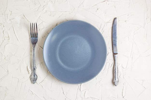 Пустая серая тарелка, вилка и нож на белом фоне. вид сверху с пространством для текста.