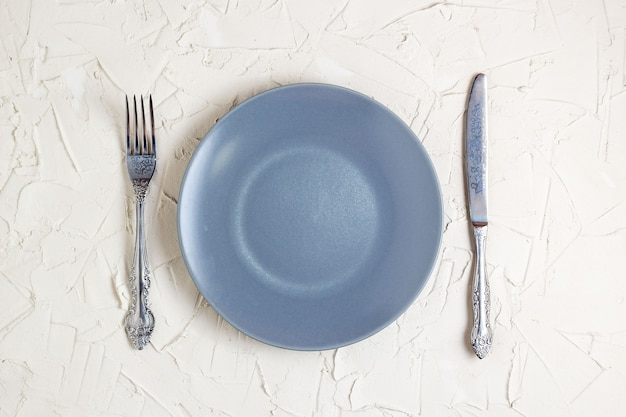 Empty grey plate, fork and knife on white background. top view with text space.