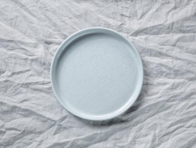 Пустая серая тарелка на фоне мятой льняной ткани, вид сверху