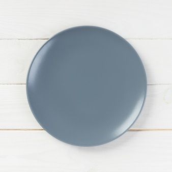 Empty grey plate on wooden
