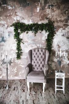 Пустое серое одиночное кресло в углу серой стены - вид спереди при естественном освещении