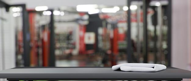 Пустая серая столешница и размытый фитнес-зал на фоне концепции макета пространства 3d-рендеринга
