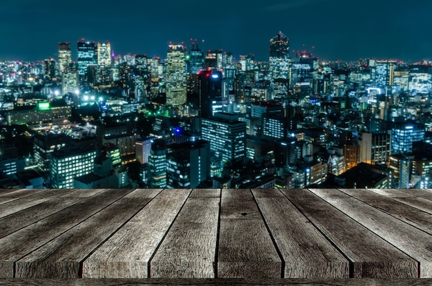Empty grey wooden table or wooden terrace with blurred image of night cityscape from business district background