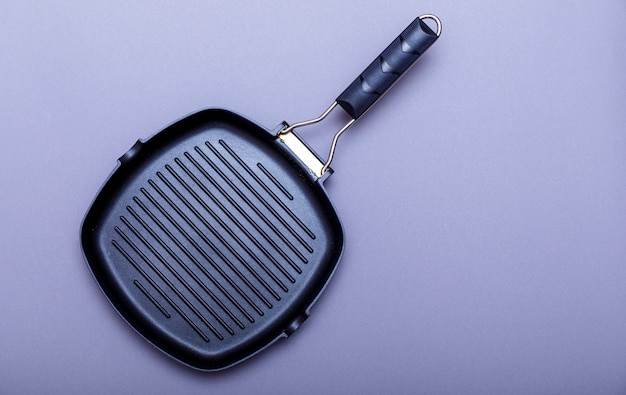 Empty grill pan on home kitchen table. metal knives on a grey background and grill