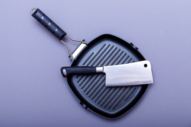 Empty grill pan on home kitchen table. metal knives, grill pan and blade. flat lay, layout.