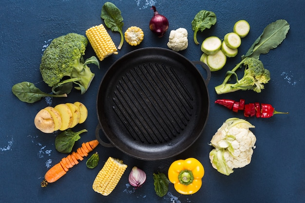 Empty grill pan with fresh vegetarian various ingredients for cooking vegan grilled food overhead view