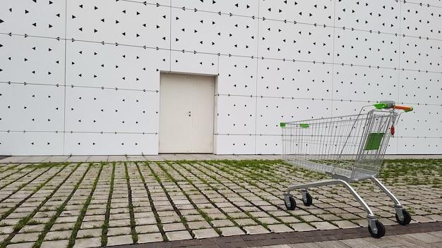 An empty grocery basket is  near the supermarket