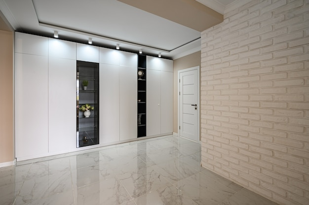 Empty hallway of modern studio apartment with white kitchen and beige bedroom
