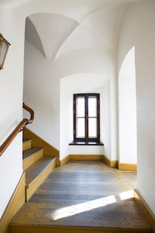 An empty hallway with a vaulted ceiling and a wooden staircase ..