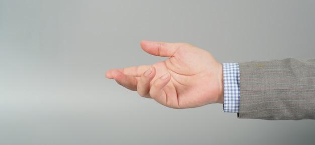 Пустой жест рукой в сером костюме на сером фоне. тема бизнесмена. крупным планом фото и студийная съемка.