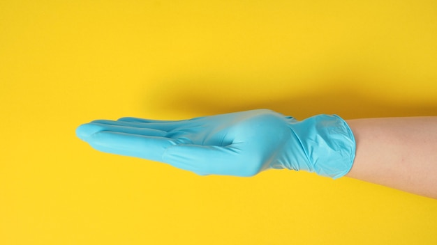 Пустая рука с перчаткой на желтом фоне.