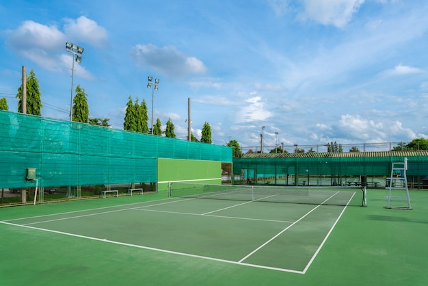Empty hard tennis court and net outdoor with blue sky clouds on a sunny day.