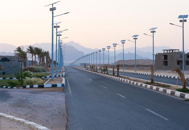 砂漠の夏の日のランタンのソーラーパネルの列とヤシの木の間の空の高速道路