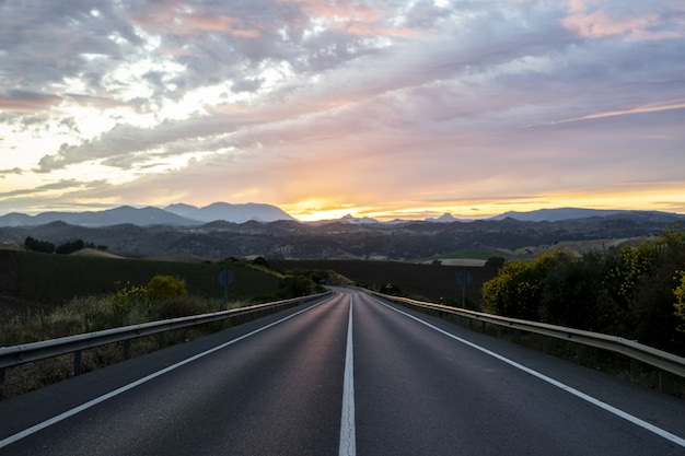 Empty highway surrounded by hills under the cloudy sunset sky