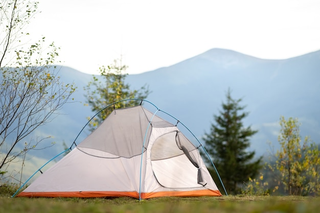 Empty hikers tent standing on campsite with view of majestic high mountain peaks in distance.