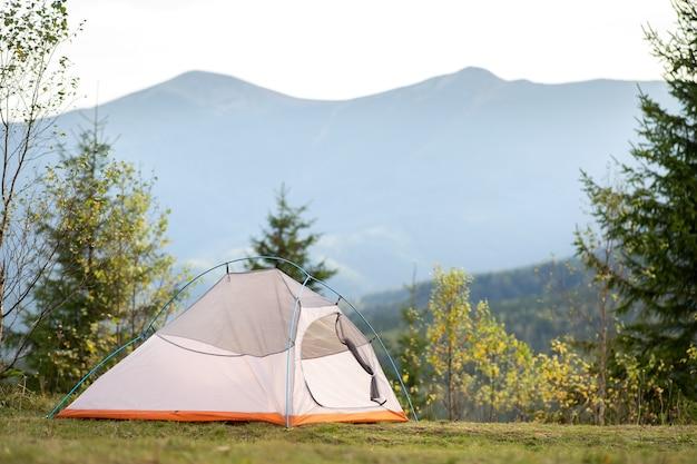 멀리 장엄한 높은 산 봉우리의 전망과 함께 캠프장에 서 있는 빈 등산객 텐트. 야생의 자연과 활동적인 여행 컨셉에서의 캠핑.
