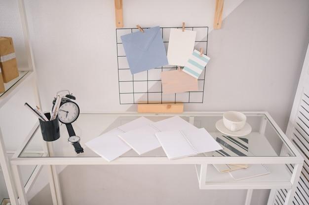Пустой домашний уютный офис рабочее пространство современный скандинавский дизайн. белый стеклянный столик, держатель-решетка для купюр со стильными элементами декора, канцелярские товары, будильник и наручные часы