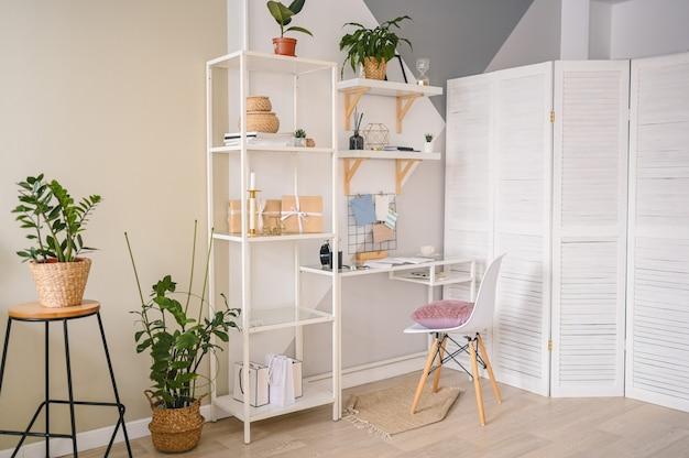 モダンなスカンジナビアデザインの居心地の良いアパートの空のホームオフィスの作業スペース。スタイリッシュな装飾要素、文房具、籐の鉢植えの観葉植物と白いテーブルチェアの棚