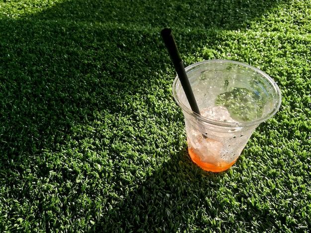 Empty iced cold thai milk tea on green grass