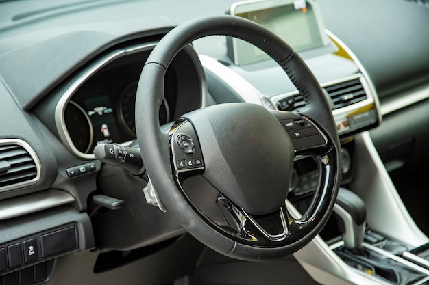 Empty interior of modern premium car dark interior close-up steering wheel and drivers seat