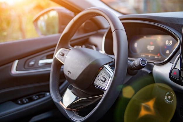Empty interior of modern premium car dark interior closeup steering wheel and drivers seat