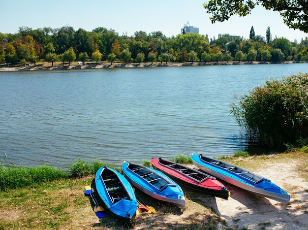 Empty kayaks on the shore of the river.