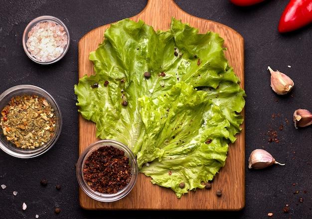 Пустая кухонная деревянная разделочная доска с зеленью, салатом и специями