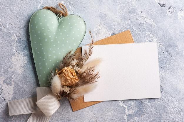 ドライフラワーとグリーンハートの花束と空のクラフト封筒。結婚式は灰色のテーブルの上のモックアップ